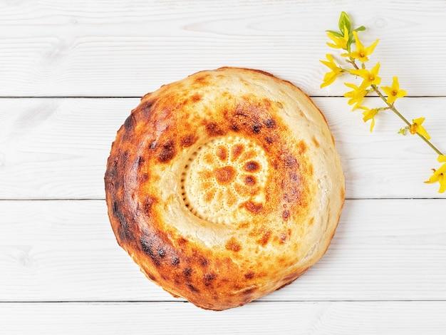 Вкусный свежий круглый хлеб тандыр на белом деревянном столе Бесплатные Фотографии