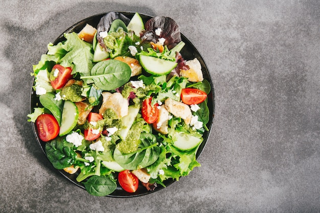 Tasty fresh salad with chicken, pesto and vegetables Premium Photo