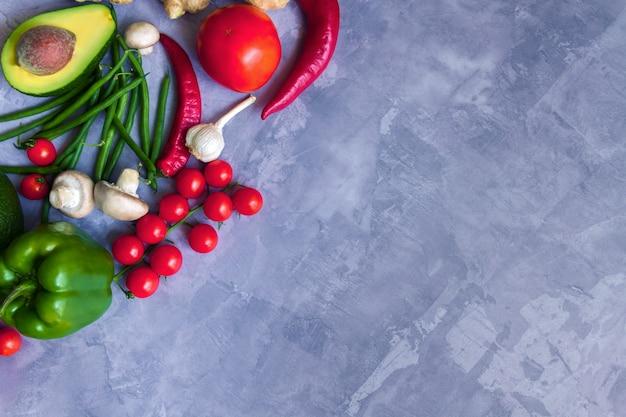 Вкусные свежие летние сырые органические антиоксидант красочные фрукты и овощи овощи: авокадо, помидоры, чеснок, перец чили, имбирь, изолированные на сером фоне. веганские и вегетарианские концепции здорового питания Premium Фотографии
