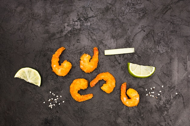 Tasty fried shrimps and juicy lemon wedges over textured concrete wall Free Photo