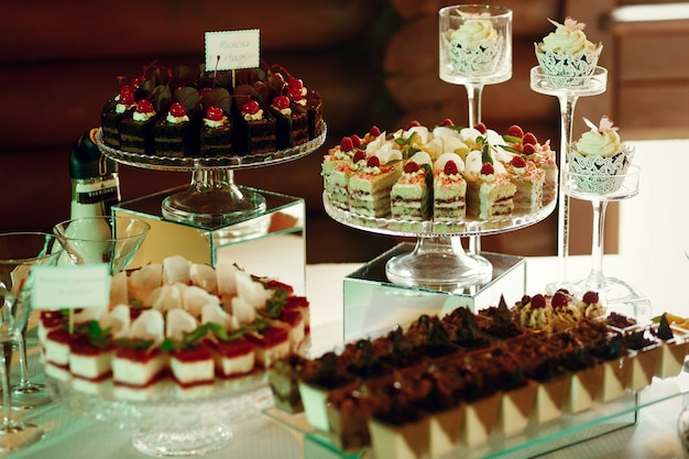 Tasty fruit and chocolate cakes stand on glass plates Photo | Free