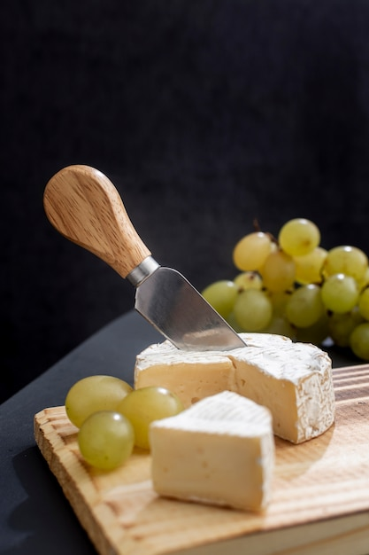 Tasty grapes with brie cheese on a board Free Photo