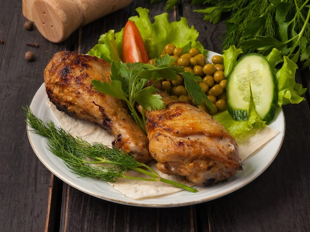하얀 접시에 야채로 장식 된 맛있는 구운 치킨 드럼 스틱 프리미엄 사진