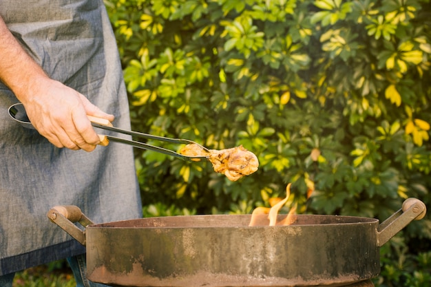 Tasty grilled meat in metal tongs on fire grill in hand Free Photo