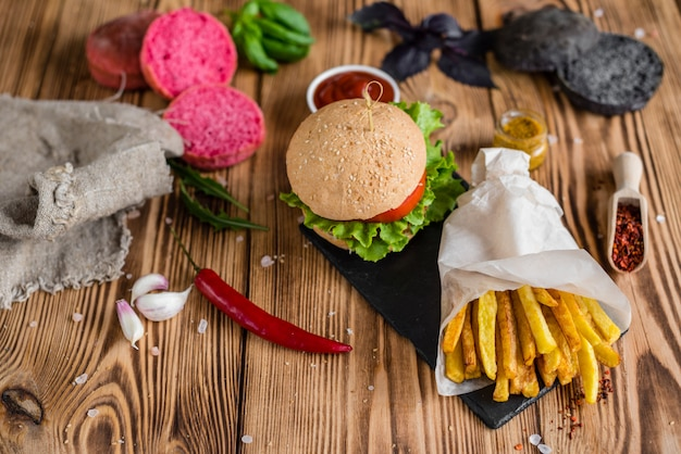 Tasty hamburger with meat and vegetables against a dark background. fast food. it can be used as a background Premium Photo