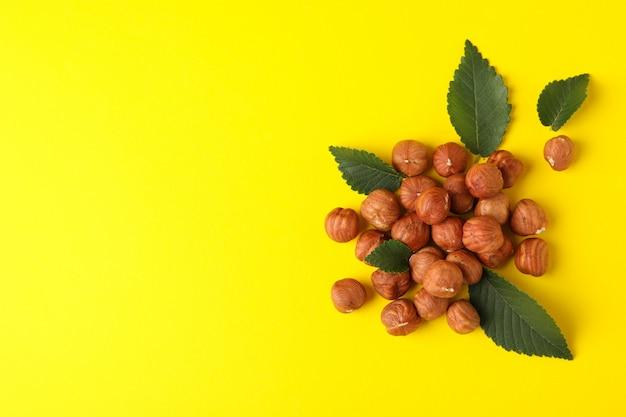 おいしいヘーゼルナッツと黄色の背景の葉。ビタミン食品 Premium写真