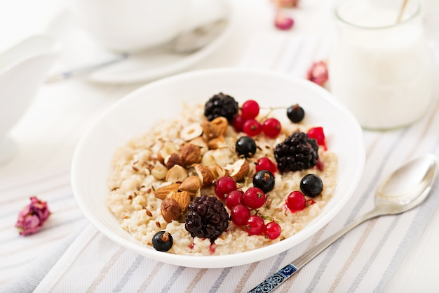 Tasty and healthy oatmeal porridge with berry, flax seeds and nuts. healthy breakfast. fitness food. Free Photo