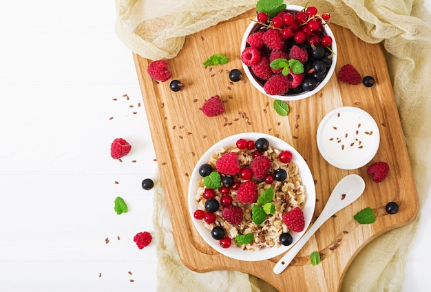 Tasty and healthy oatmeal porridge with berry, flax seeds and yogurt. healthy breakfast.  proper nutrition. flat lay. top view. Premium Photo