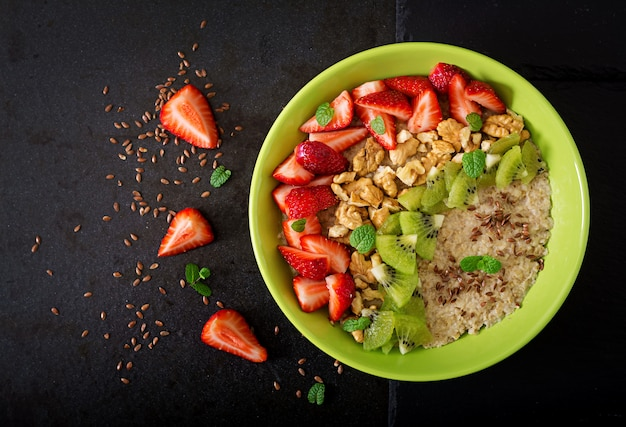 Tasty and healthy oatmeal porridge with berry, nuts and flax seeds. healthy breakfast. fitness food. proper nutrition. flat lay. top view Premium Photo