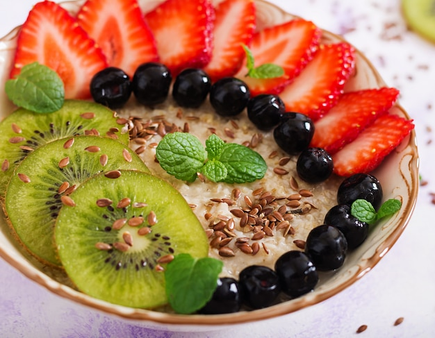Tasty and healthy oatmeal porridge with fruit, berry and flax seeds. healthy breakfast. fitness food. proper nutrition. Free Photo