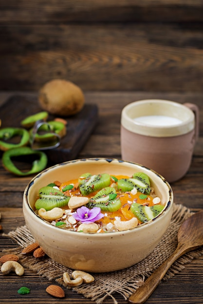 Tasty and healthy oatmeal porridge with fruit, berry and nuts. healthy breakfast. fitness food. proper nutrition Premium Photo