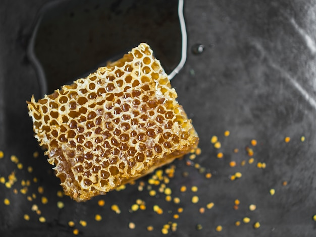 Tasty honeycomb piece and bee pollens on black backdrop Free Photo