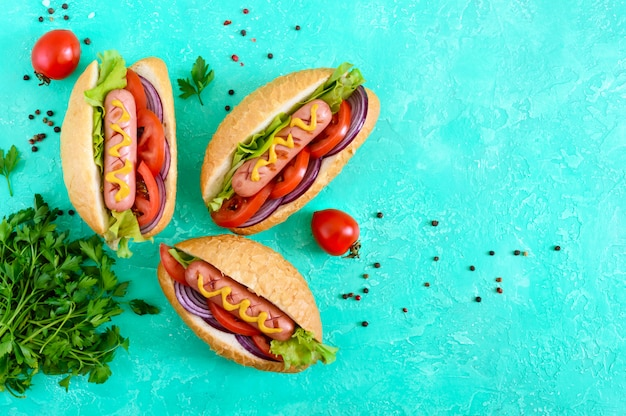 Вкусные хот-доги. жареная колбаса с помидорами, красным луком, листьями салата, горчицей в хрустящей буханке. уличная забегаловка. быстрое питание. вид сверху Premium Фотографии