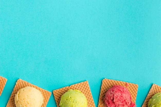 Tasty ice cream scoop on square waffles on turquoise surface Free Photo