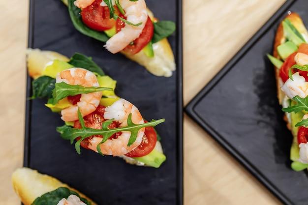 Вкусные итальянские брускеты-закуски с помидорами, анчоусами, прошутто, моцареллой, креветками и морепродуктами. Premium Фотографии