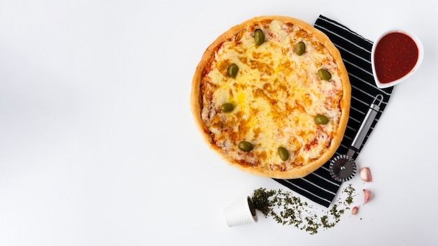 Tasty italian pizza and tomato sauce with pizza cutter on placemat over white background Free Photo