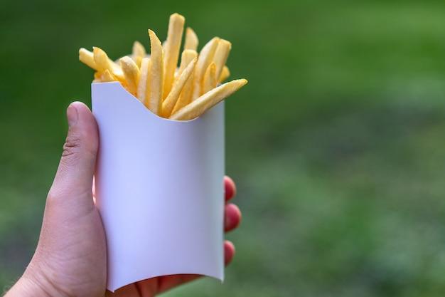 자연 야외에 남자 손에 흰 종이 상자에 맛있는 육즙이 감자 튀김. 패스트 푸드 모형 Ongreen 배경입니다. 텍스트를위한 공간이 건강에 해로운 음식 개념. 튀긴 감자 메뉴. 프리미엄 사진