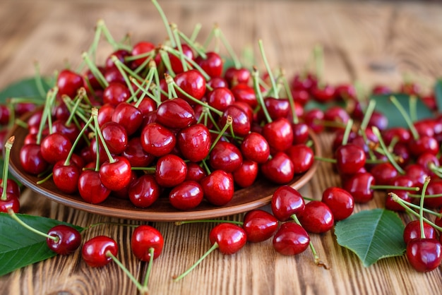 Tasty juicy sweet cherry on a wooden background. it can be used as a background Premium Photo