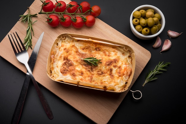 Tasty lasagna and ingredient on wooden cutting board over black surface Free Photo