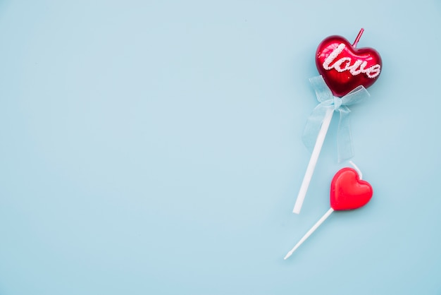 Tasty lollipop and decorative candle on wands in form of hearts Free Photo