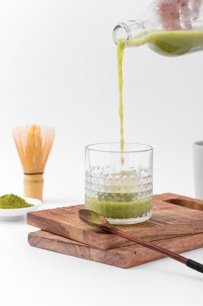 Tasty matcha tea pouring into glass Free Photo
