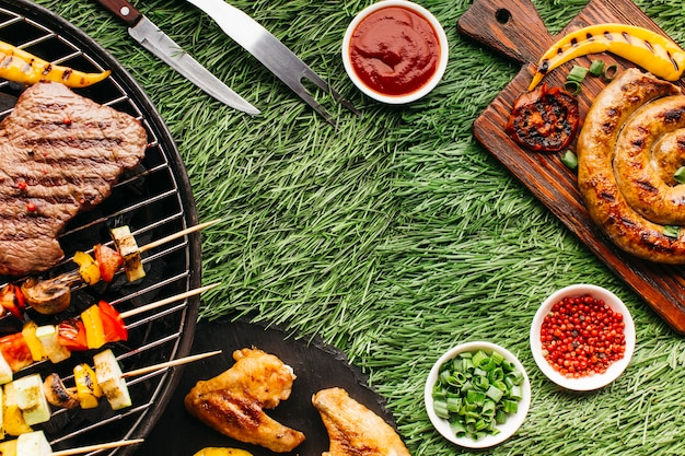 Tasty meal with grilled meat and kebab skewer on grass backdrop Free Photo