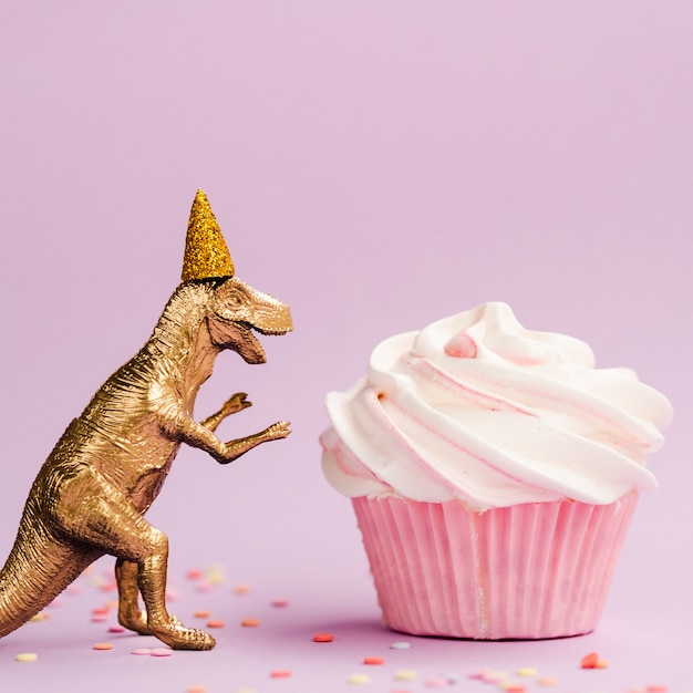 Tasty muffin and dinosaur with birthday hat Free Photo