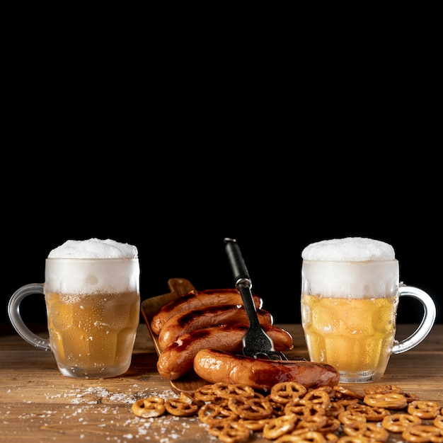Tasty mugs of beer with sausages on a table Free Photo