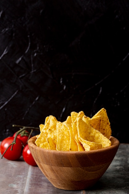 Tasty nachos in wooden bowl and tomatoes Free Photo