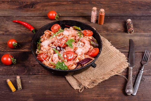 Tasty pasta with shrimp and tomato on a frying pan Premium Photo