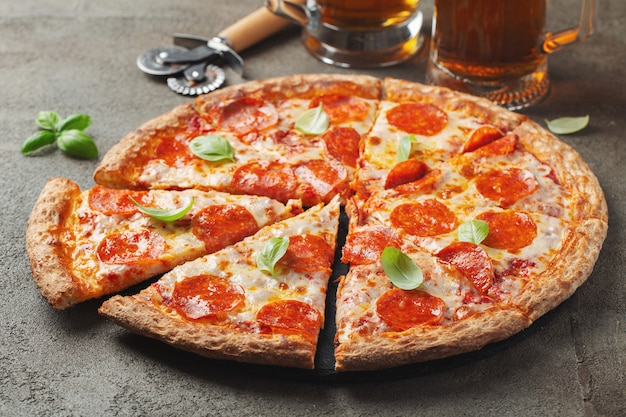 Tasty pepperoni pizza with basil and glass of beer on brown concrete background. Premium Photo