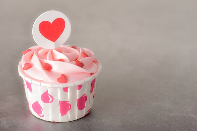 Tasty pink pastel butter cream cupcakes on red background Premium Photo