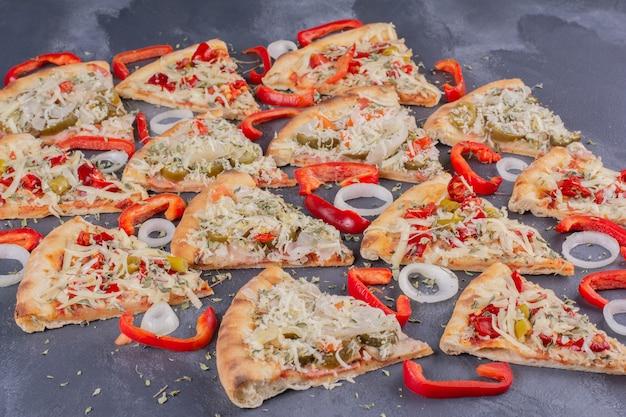 オニオンリングとコショウを添えた青のおいしいピザスライス。 無料写真