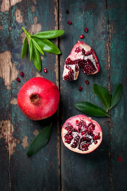 Tasty pomegranate with green leaves Free Photo