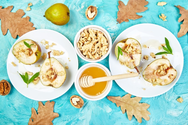 Tasty roast pears with honey and walnuts on blue background table. Premium Photo
