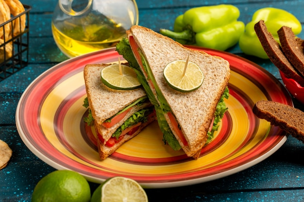 Tasty sandwiches with green salad tomatoes along with green bell-pepper bread and lemon on blue Free Photo