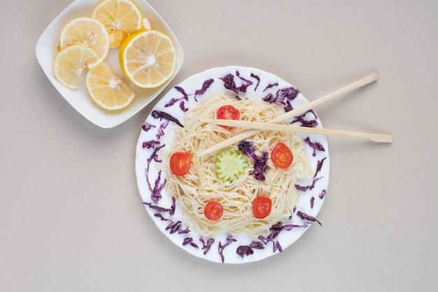 흰색 표면에 맛있는 스파게티와 레몬 조각 무료 사진