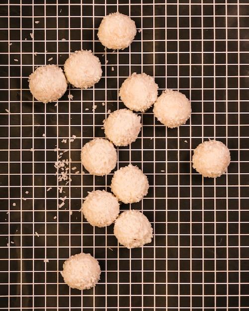 Tasty sweet coconut balls on checkered textile Free Photo