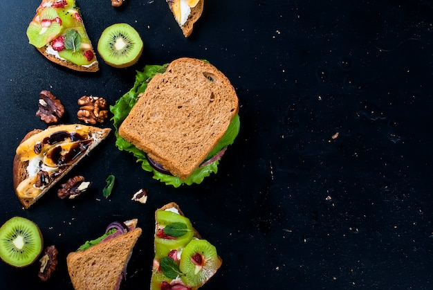 Tasty sweet sandwiches with bananas, nuts and chocolate, kiwi, strawberries and mint on black background Premium Photo