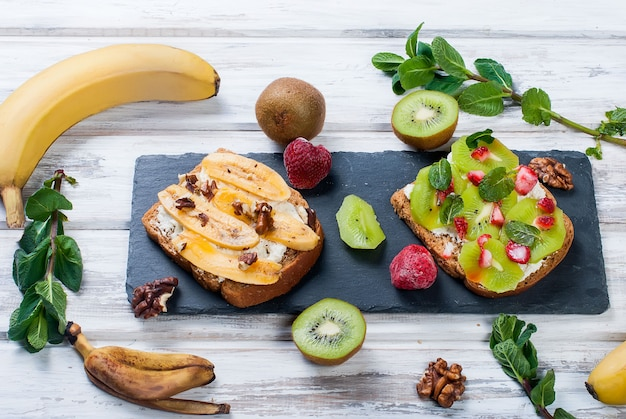 Tasty sweet sandwiches with bananas, nuts and chocolate, kiwi, strawberries and mint on wooden table Premium Photo