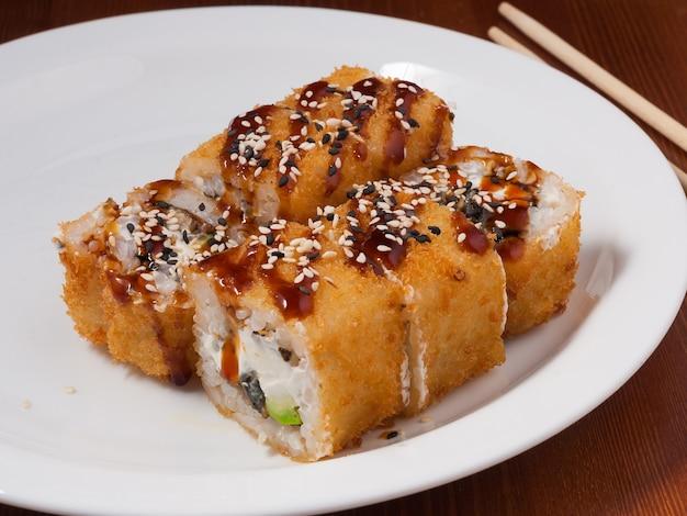 白い皿にうなぎが入った美味しい天ぷら巻き寿司 Premium写真