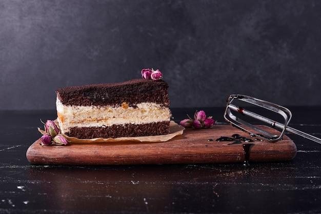 Gustosa torta tiramisù con semi di fiori su sfondo scuro. Foto Gratuite