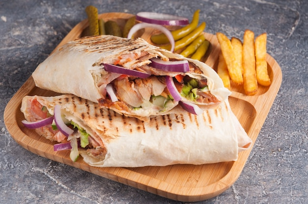 Tasty turkish shawarma with chicken and vegetables with onions Premium Photo