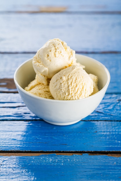 Tasty vanilla ice scoops in bowl on blue wooden rustic table. closeup. Free Photo