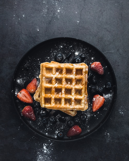 Tasty waffle with strawberries and sugar, top view Free Photo