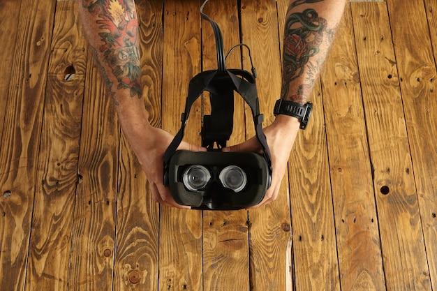 Tattoed 손을 잡고 Vr 안경을 거꾸로, 소박한 나무 보드에 고립 된 새로운 기술의 프리젠 테이션 무료 사진