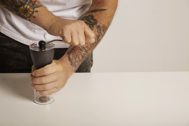 A tattoed man in white t-shirt and black jeans grinds coffee beans in a modern slim manual burr grinder, close up Free Photo