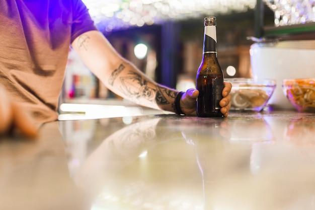 Tattoo man holding alcohol bottle on reflective table Free Photo