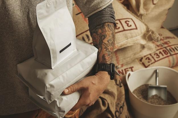 Il barista tatuato tiene i sacchetti vuoti del pacchetto con i chicchi di caffè appena sfornati pronti per la vendita e la consegna Foto Gratuite