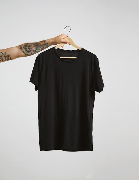 Татуированная рука байкера держит вешалку с пустой черной футболкой из тонкого хлопка премиум-класса, изолированной на белом Бесплатные Фотографии